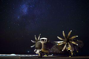 A COD sits aboard the USS Enterprise beneath a star-strewn night sky. (U.S. Navy photo by Mass Communication Specialist 2nd Class Brooks B. Patton Jr./Released)